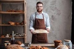 Жизнерадостный хлебопек молодого человека стоя на хлебопекарне держа хлеб стоковые изображения