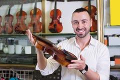 Жизнерадостный человек покупая традиционные скрипки Стоковая Фотография RF