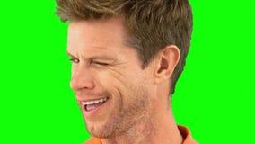 Жизнерадостный человек подмигивая глазу на зеленом экране видеоматериал