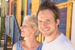 Жизнерадостный человек при мать стоя против хаты пляжа стоковое фото rf