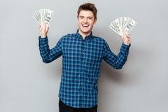 Жизнерадостный человек стоя над серой стеной держа деньги стоковая фотография rf