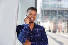Жизнерадостный человек стоя против стены говоря на умном телефоне Стоковое Изображение