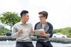 2 жизнерадостных азиатских бизнесмены обсуждая с документами Стоковая Фотография