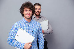2 жизнерадостных бизнесмена держа папки Стоковая Фотография RF