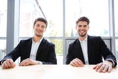 2 жизнерадостных бизнесмена сидя на таблице в офисе Стоковые Фотографии RF
