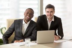 2 жизнерадостных бизнесмена смотря камеру, multiracial дело Стоковая Фотография