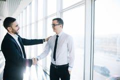 2 жизнерадостных бизнесмена тряся руки и усмехаться Стоковое Фото