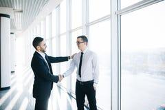 2 жизнерадостных бизнесмена тряся руки и усмехаясь на заднем плане Стоковая Фотография