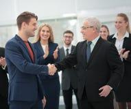 2 жизнерадостных бизнесмены тряся руки пока их коллега Стоковое Фото