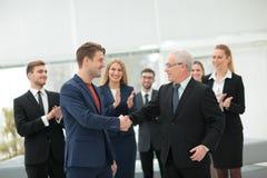 2 жизнерадостных бизнесмены тряся руки пока их коллега Стоковое Изображение RF