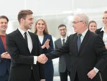 2 жизнерадостных бизнесмены тряся руки пока их коллега Стоковые Изображения RF