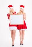 2 жизнерадостных близнеца сестер представляя с пустой доской Стоковое Изображение RF