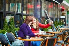 2 жизнерадостных девушки в парижском кафе улицы Стоковые Фото