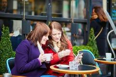 2 жизнерадостных девушки в парижском кафе улицы Стоковые Изображения