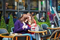 2 жизнерадостных девушки в парижском кафе улицы Стоковое Изображение