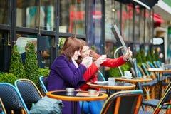 2 жизнерадостных девушки в парижском кафе улицы Стоковые Фотографии RF