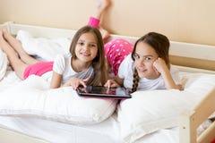 2 жизнерадостных девушки лежа на кровати и используя таблетку Стоковое Изображение