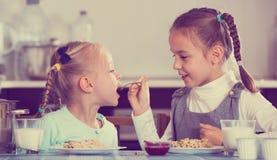 2 жизнерадостных девушки есть здоровую овсяную кашу Стоковое Изображение