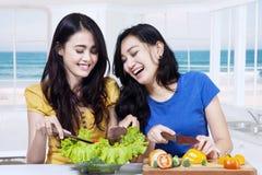 2 жизнерадостных девушки делая салат Стоковая Фотография RF