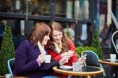 2 жизнерадостных девушки принимая selfie в парижском кафе Стоковые Фото