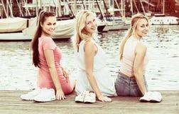3 жизнерадостных девушки сидя на пристани в городке Стоковые Фотографии RF