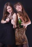 2 жизнерадостных девушки с шампанским и стеклами Стоковое Изображение
