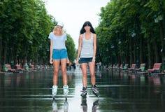 2 жизнерадостных девушки rollerblading Стоковые Изображения