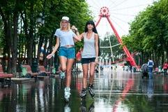 2 жизнерадостных девушки rollerblading Стоковые Фото