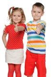 2 жизнерадостных дет держат его большие пальцы руки вверх Стоковые Изображения RF