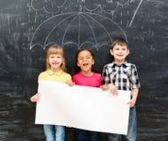3 жизнерадостных дет держа белый пустой бумажный лист Стоковое фото RF