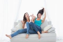 2 жизнерадостных женских друз сидя на софе в живущей комнате Стоковое Изображение RF