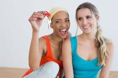 2 жизнерадостных женских друз с ключами дома Стоковая Фотография
