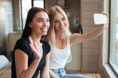 2 жизнерадостных женщины внутри помещения используя мобильный телефон и развевать Стоковая Фотография RF