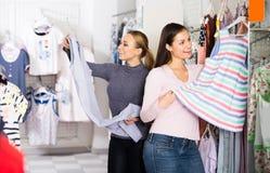 2 жизнерадостных женщины выбирая одежды спать Стоковые Фото