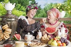 2 жизнерадостных женщины выпивая чай с бейгл и вареньем outdoors Стоковое фото RF