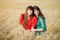 2 жизнерадостных женщины в пшеничном поле на заходе солнца в голубом и красном длинном платье воздуха Стоковая Фотография