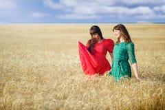 2 жизнерадостных женщины в пшеничном поле на заходе солнца в голубом и красном длинном платье воздуха Стоковые Фотографии RF