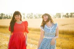 2 жизнерадостных женщины в пшеничном поле на заходе солнца в голубом и красном длинном платье воздуха Стоковые Изображения RF