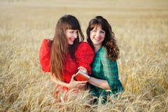 2 жизнерадостных женщины в пшеничном поле на заходе солнца в голубом и красном длинном платье воздуха Стоковые Изображения