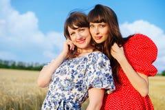 2 жизнерадостных женщины в пшеничном поле на заходе солнца в голубом и красном длинном платье воздуха Стоковое Изображение RF