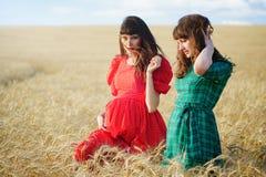 2 жизнерадостных женщины в пшеничном поле на заходе солнца в голубом и красном длинном платье воздуха Стоковое Изображение