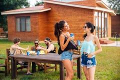 2 жизнерадостных женщины говоря и смеясь над на партии лета внешней Стоковое Изображение RF