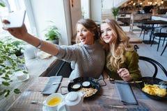 2 жизнерадостных женщины делая фото selfie Стоковые Фотографии RF