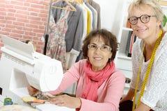 2 жизнерадостных женщины работая совместно в их Стоковое Фото