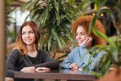 2 жизнерадостных женщины сидя в кафе и усмехаться Стоковое Изображение RF