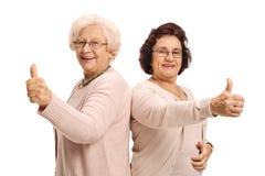 2 жизнерадостных зрелых женщины держа их большие пальцы руки вверх Стоковое Фото