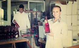 2 жизнерадостных коллеги держа бутылки вина Стоковая Фотография