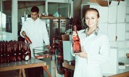 2 жизнерадостных коллеги держа бутылки вина Стоковое Фото