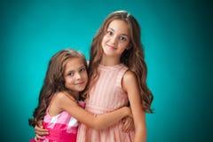 2 жизнерадостных маленькой девочки на оранжевой предпосылке Стоковое Фото