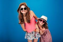 2 жизнерадостных милых сестры в солнечных очках и шляпах Стоковые Изображения